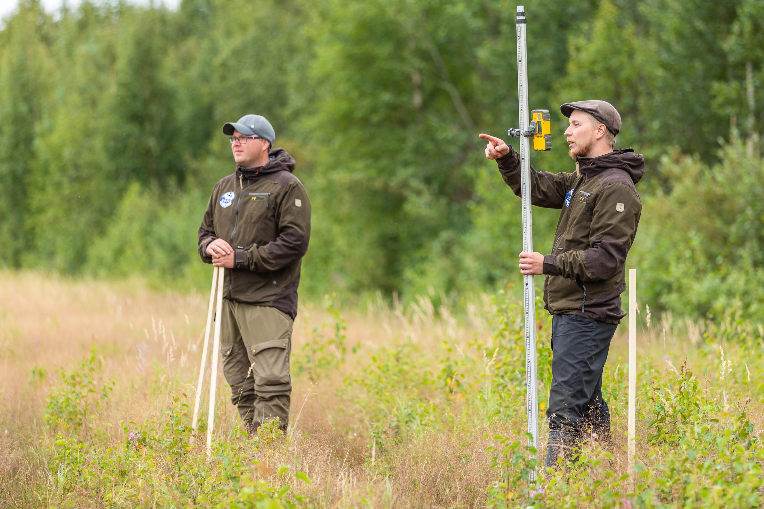 Kaksi kosteikkosuunnittelijaa seisovat niittymäisellä kosteikolla käsissään mittausvälineitä.